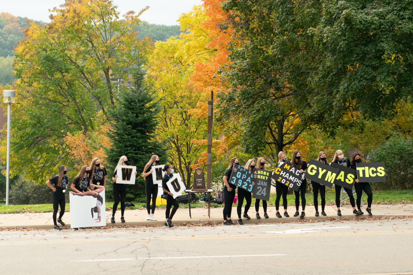 The WMU gymnastics team holds signs along the side of the road.