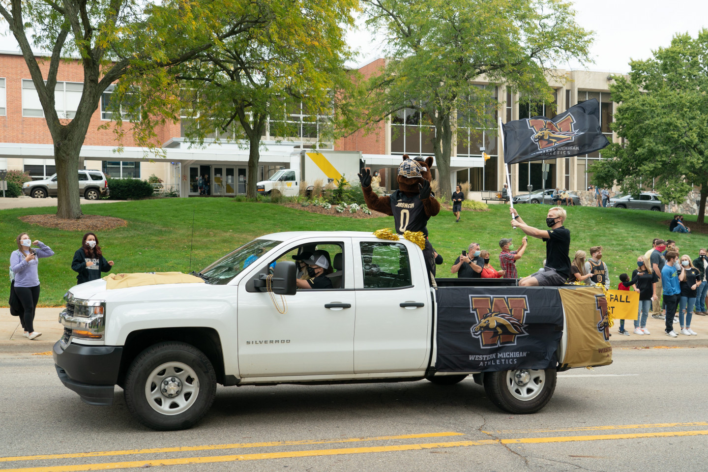 Buster Bronco rides in a truck during the parade.