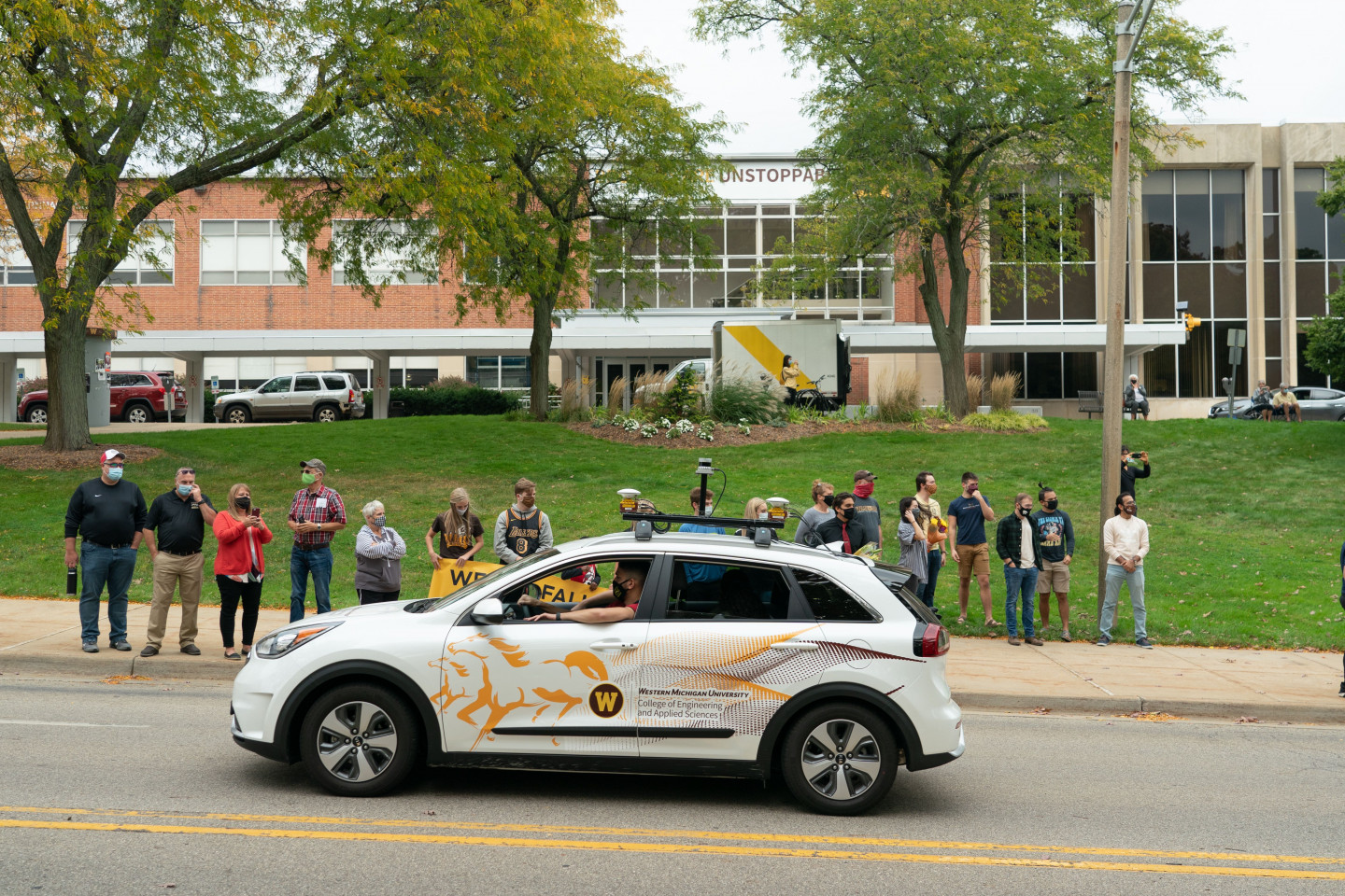 The College of Engineering and Applied Sciences' car drives down the parade route.
