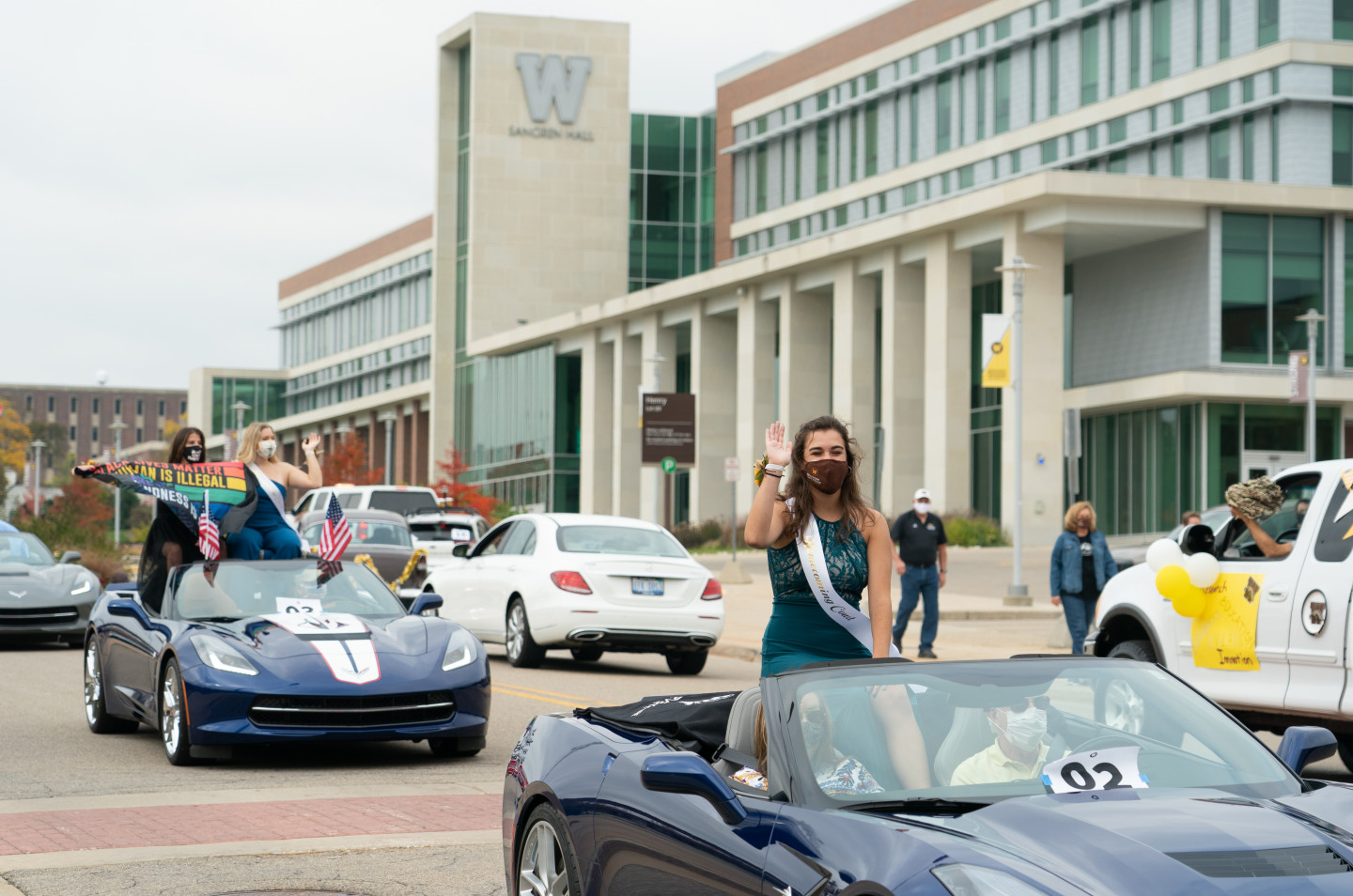 Members of the Homecoming Court ride in convertibles by Sangren Hall.