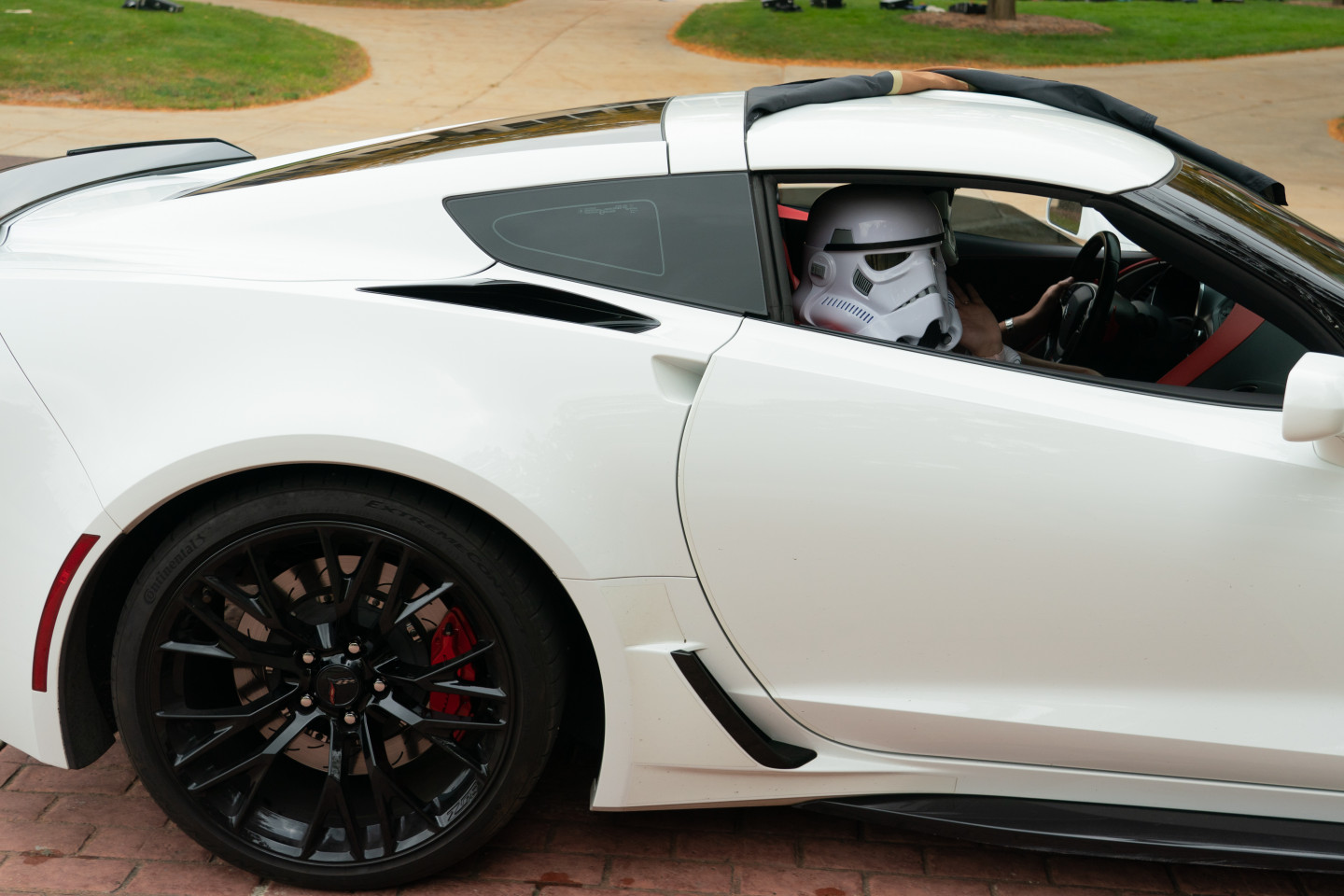 A Storm Trooper rides in the passenger seat of a car.