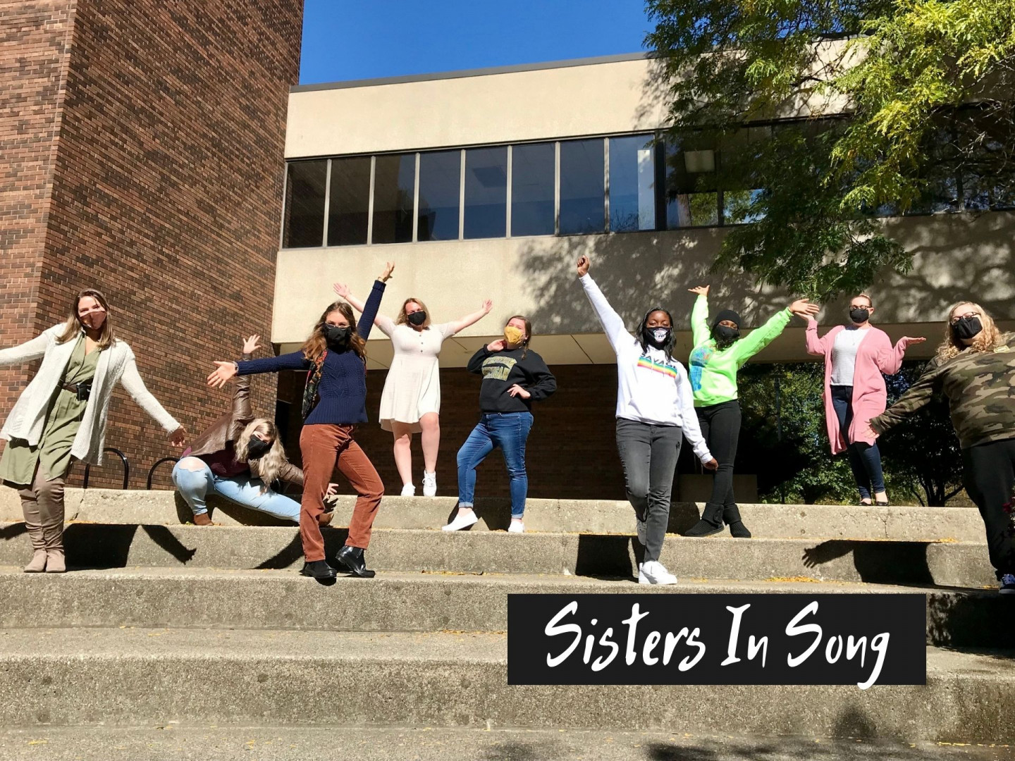 Students pose for a picture on steps on campus.
