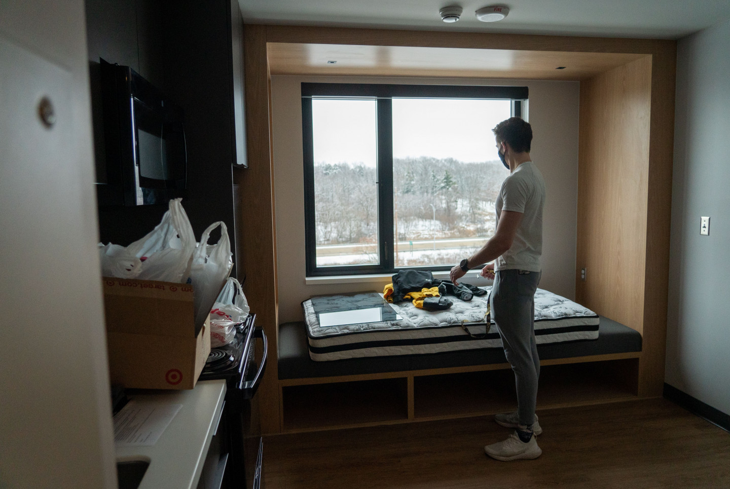 A student stands by a large window in his apartment.