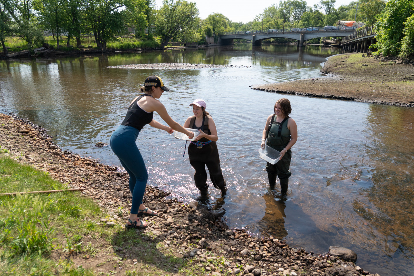 Students stand in the Kalamazoo River.