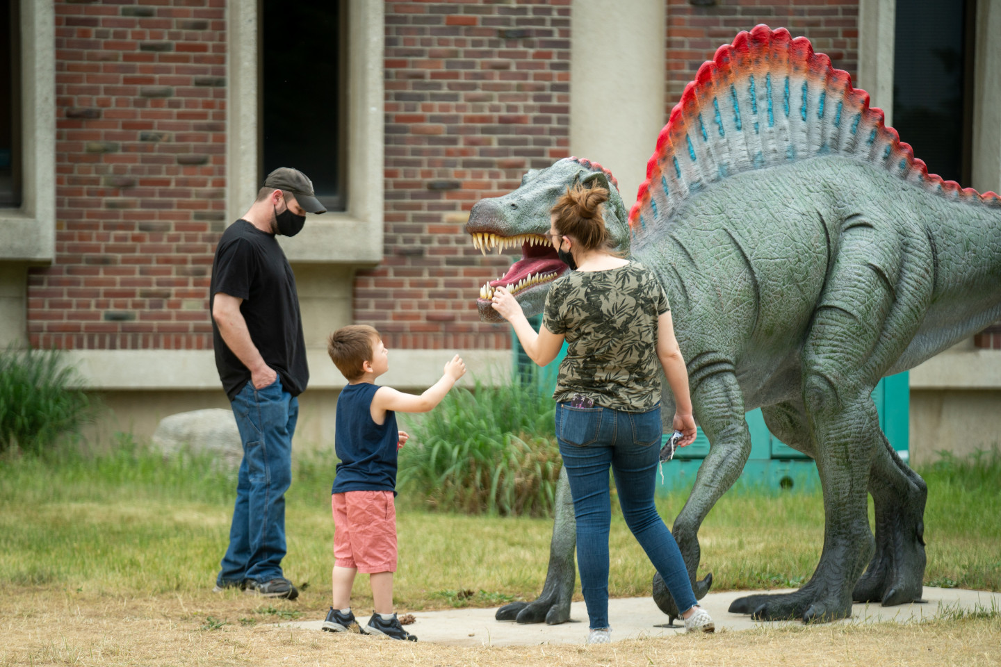 A family looks at the spinosaurus statue.