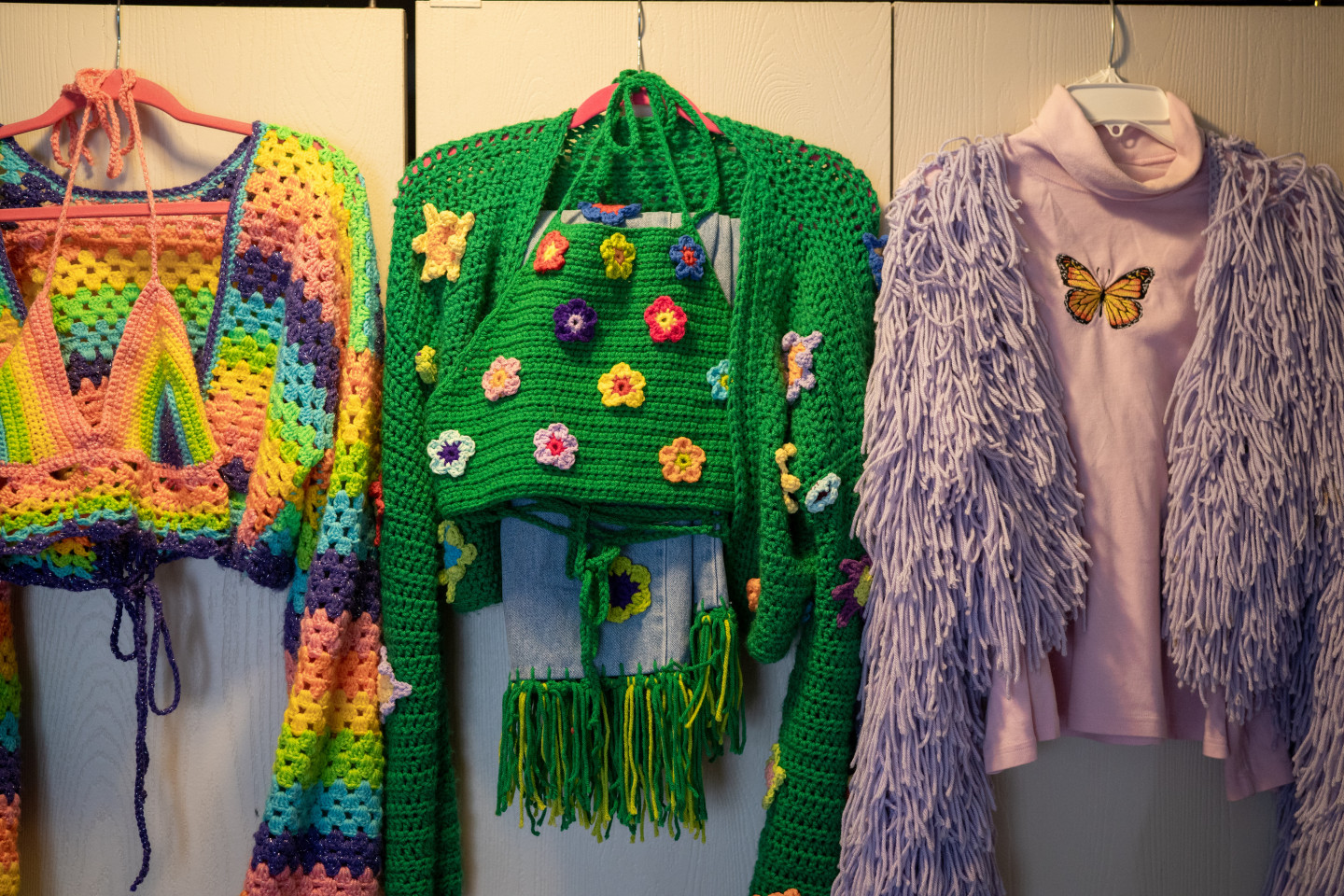 Several crocheted outfits on hangers.