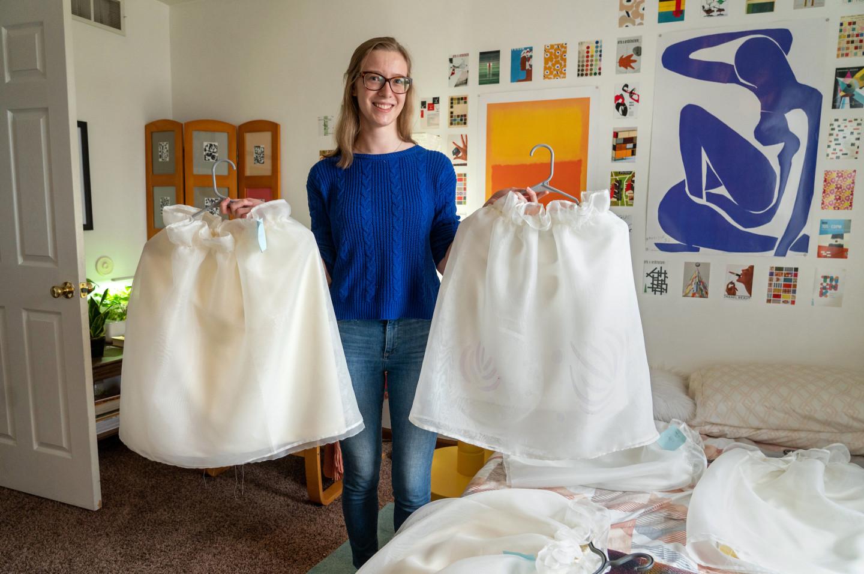 Julia LeKander holds skirts on hangers.