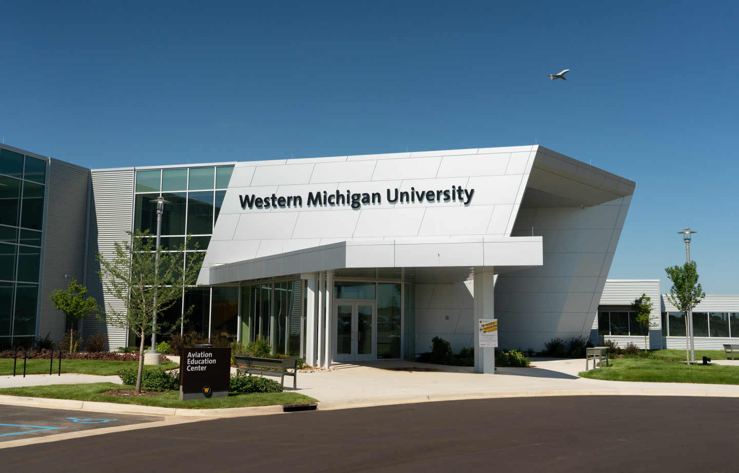An airplane flies over the Aviation Education Center.