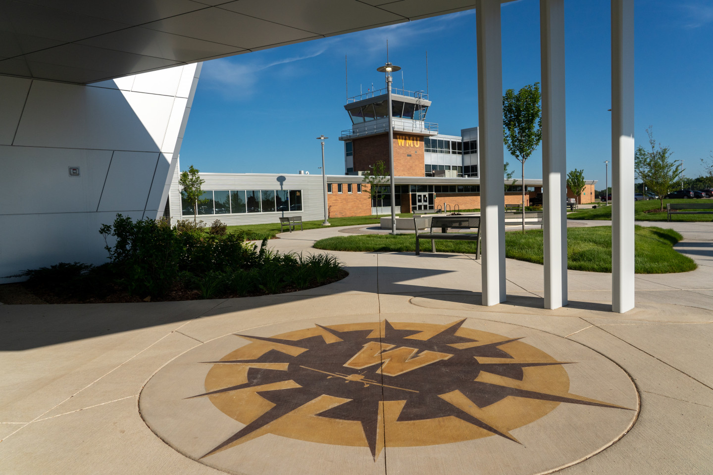 """Artwork featuring a """"W"""" and airplane on the ground outside the Aviation Education Center."""