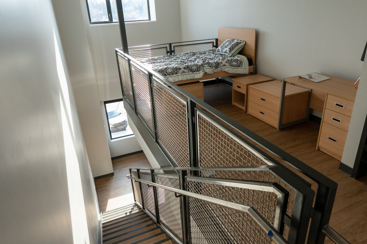 A bed in a loft area of an apartment.