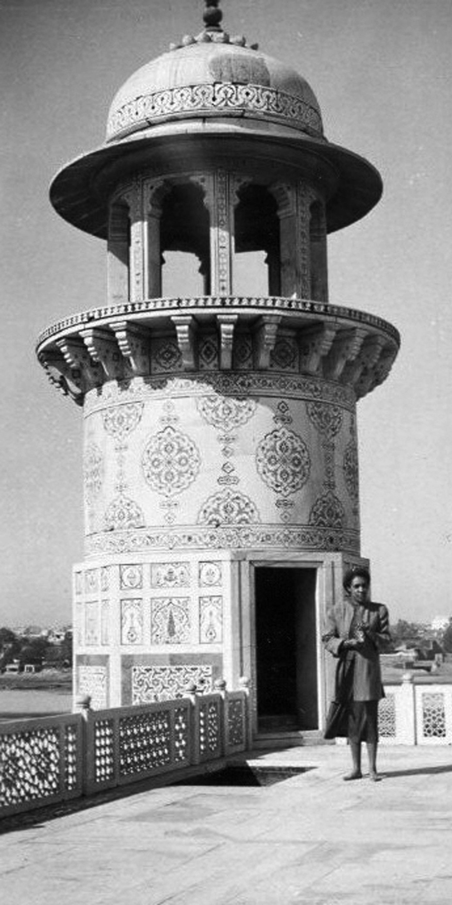 Merze Tate poses next to a tower.