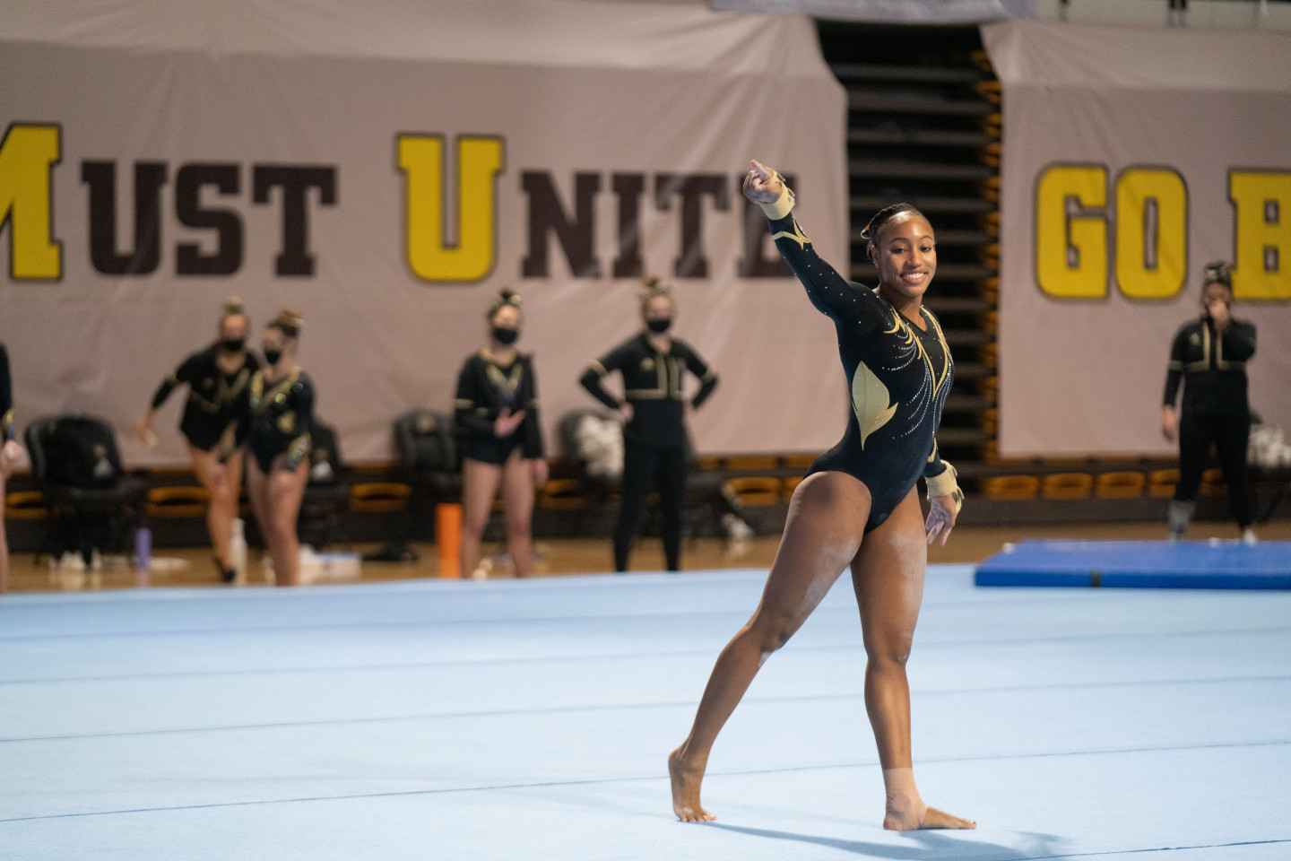 Stacie Harrison waves to the crowd during a meet.