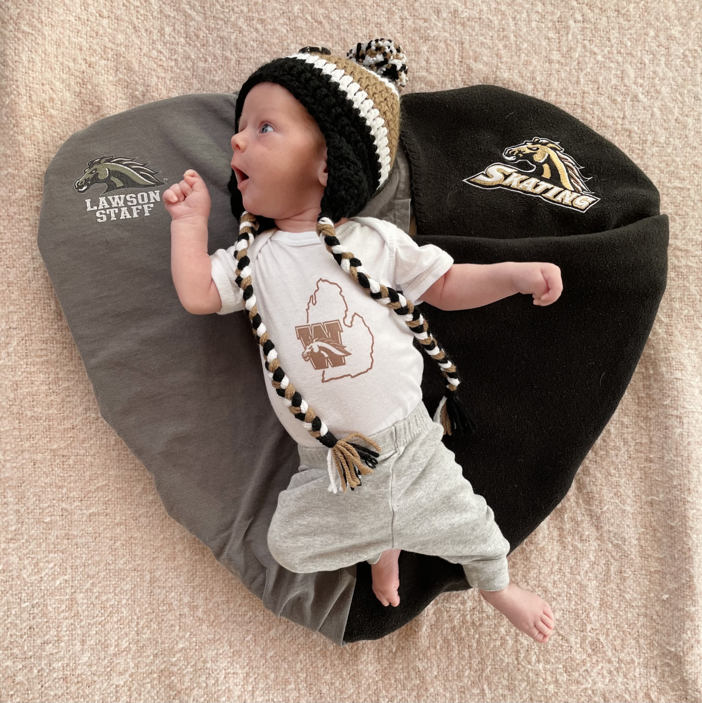 A baby lays on a heart made by two t-shirts.