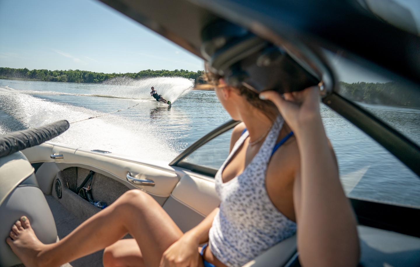 A boat passenger looks back at a person water skiing behind the boat.