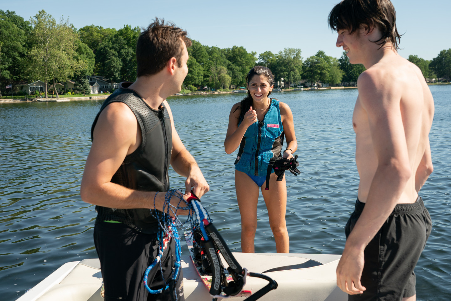 Three people in swimsuits stand by the water.