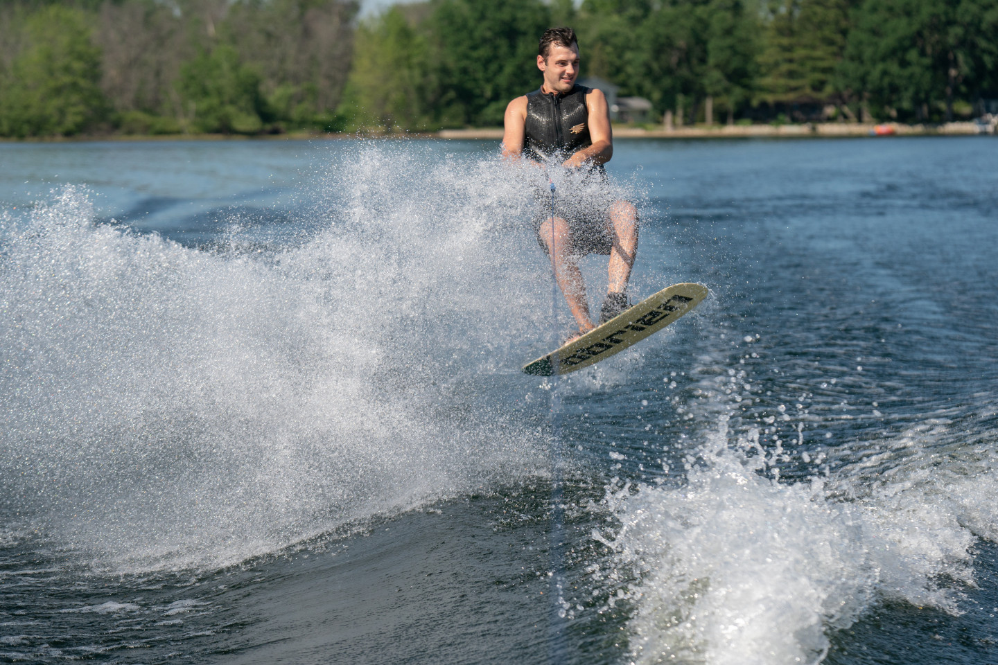 A person jumps out of the water on a wakeboard.