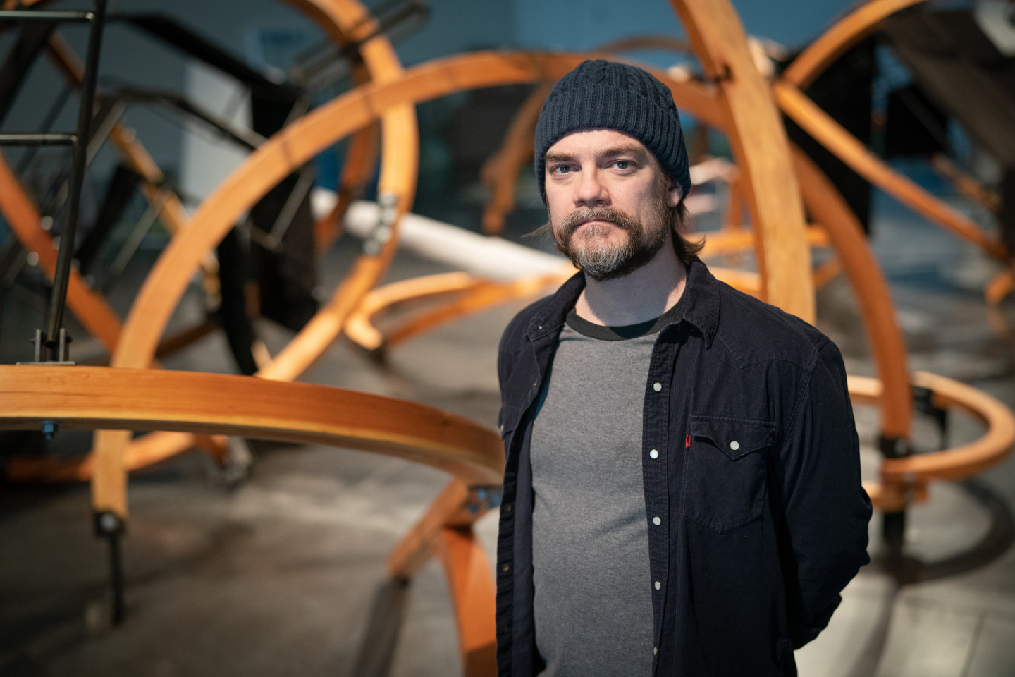 """Artist Patrick Wilson stands in front of his sculpture """"Black Tent Transit."""""""