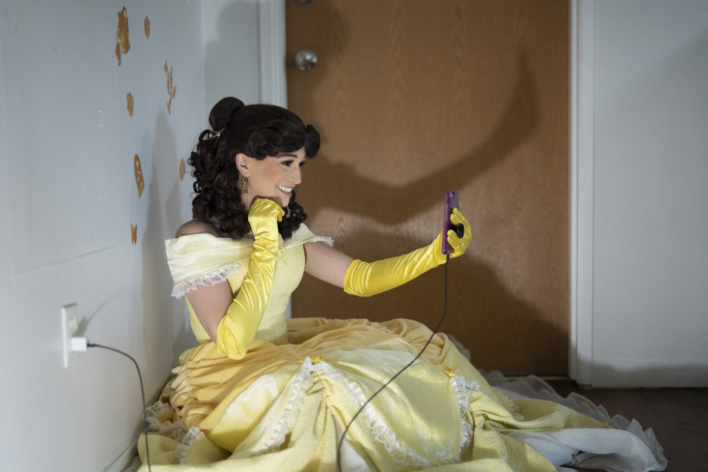 A student dressed as Belle from Beauty and the Beast smiles into her phone during a video call.