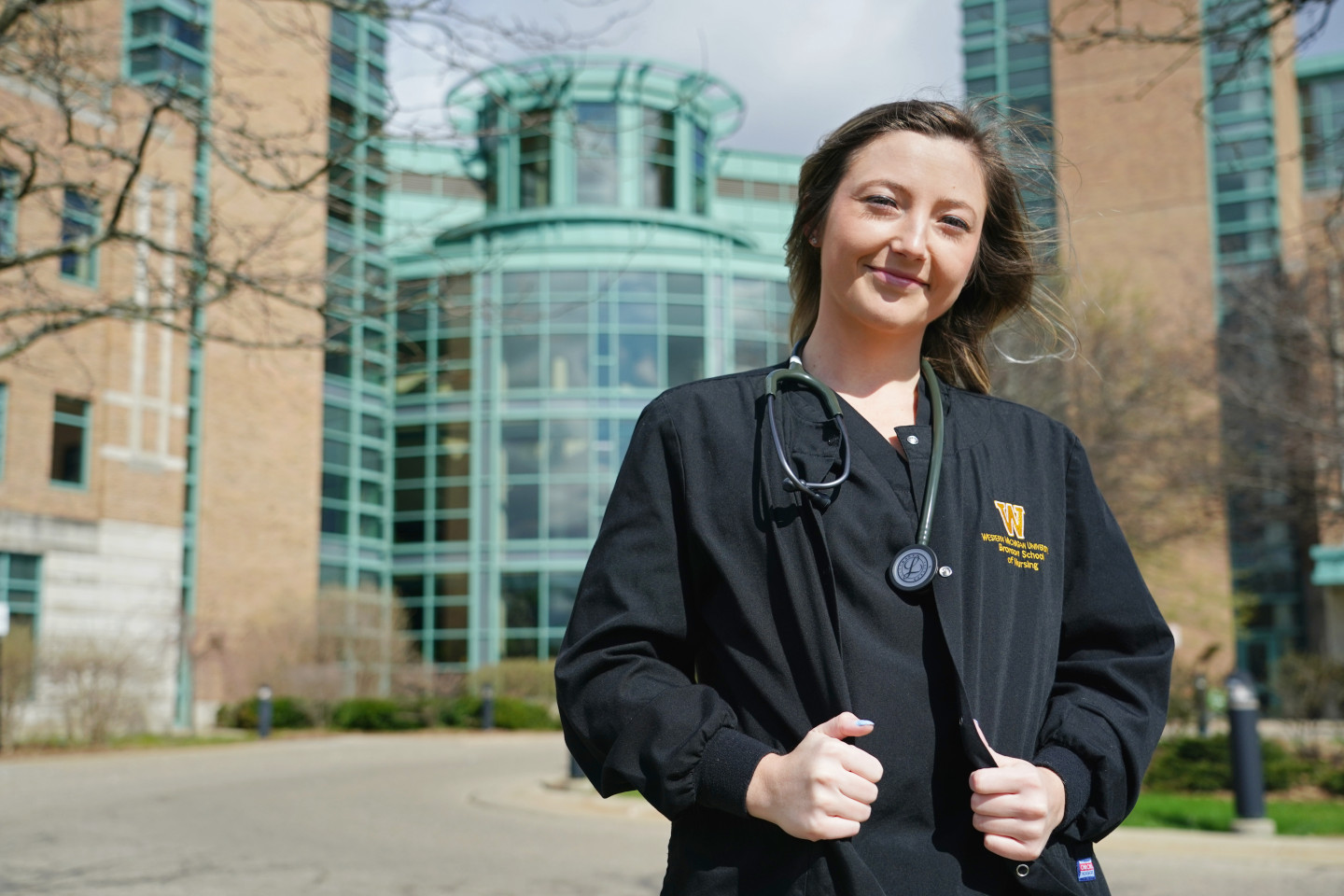 A nursing student wearing a stethoscope stands outside Bronson Hospital.
