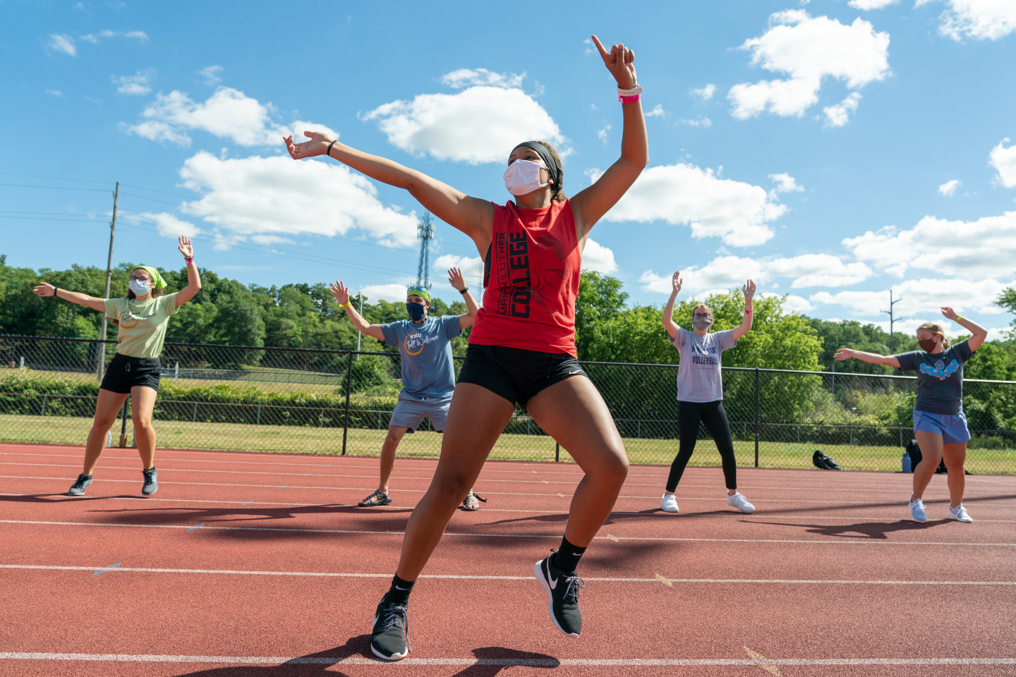 Five students wearing masks participate in an outdoor fitness class.