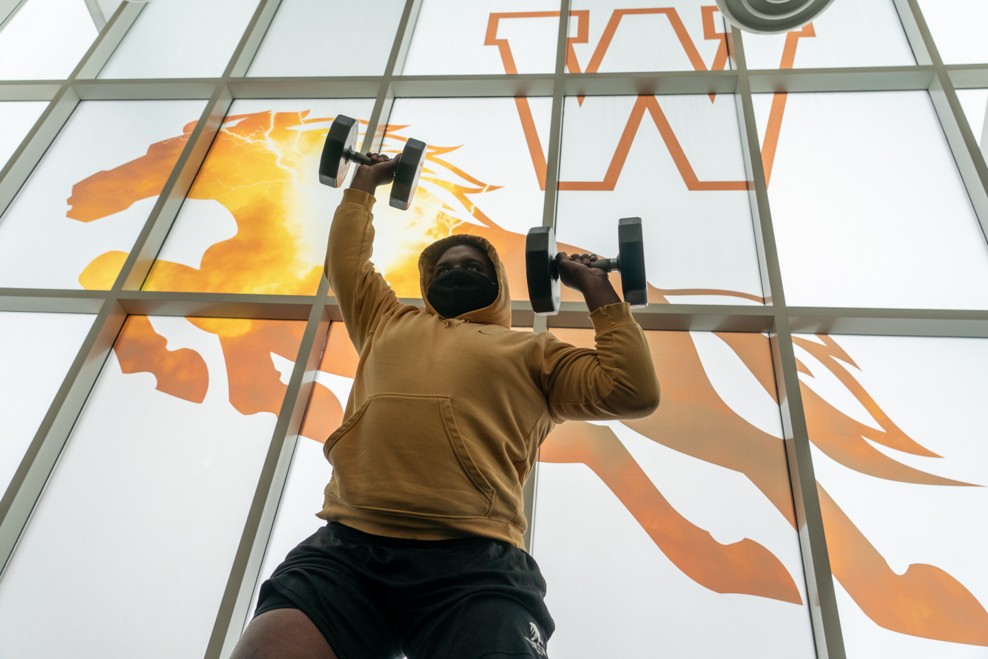 A man wearing a mask while lifting weights in front of the window of the Student Recreation Center.