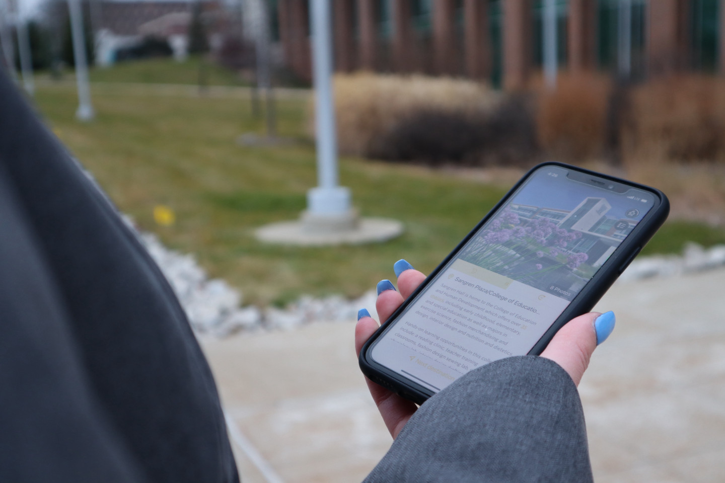 A woman holds a phone with the campus tour app open.
