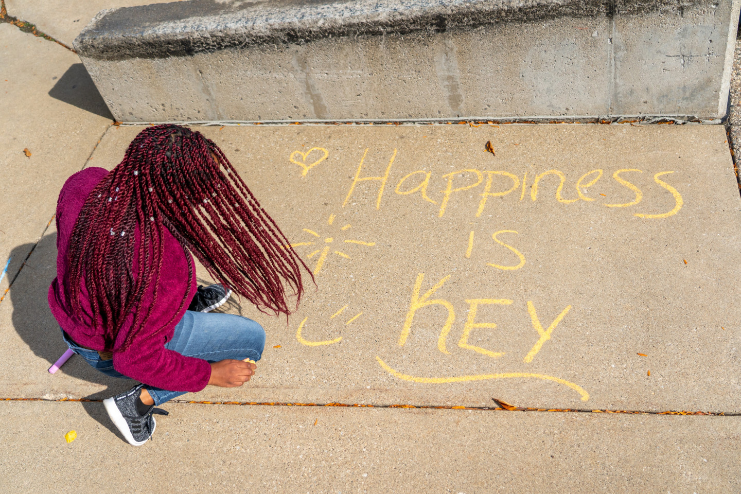 """A student writes """"Happiness is key"""" in chalk on the sidewalk."""