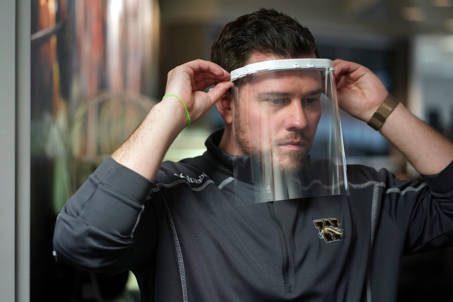 A staff member fits a face shield on his head.