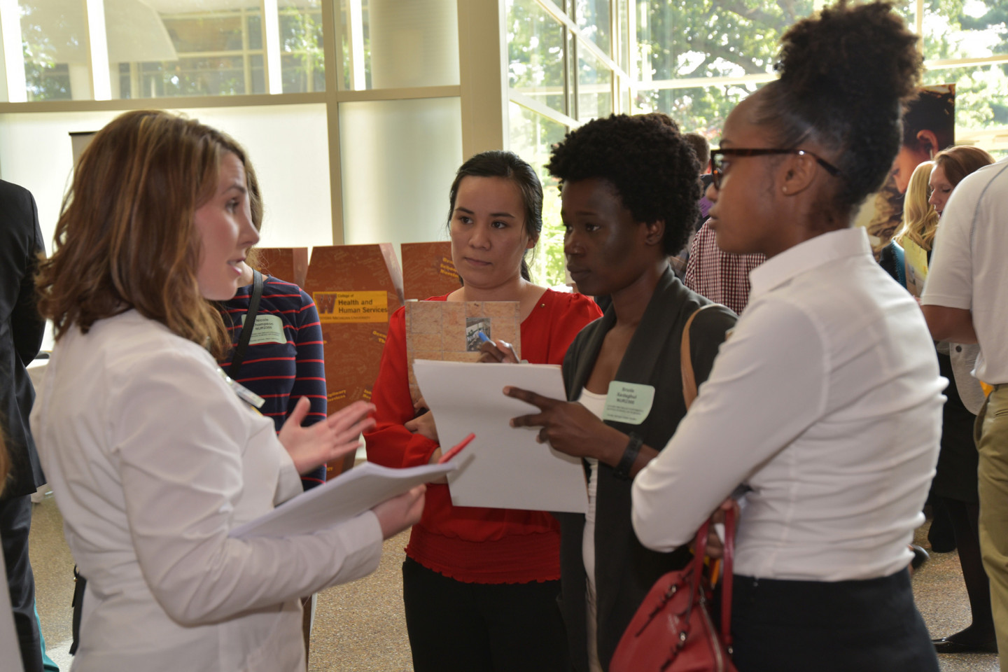 A diverse group of WMU nursing students talks with a professional at an event.