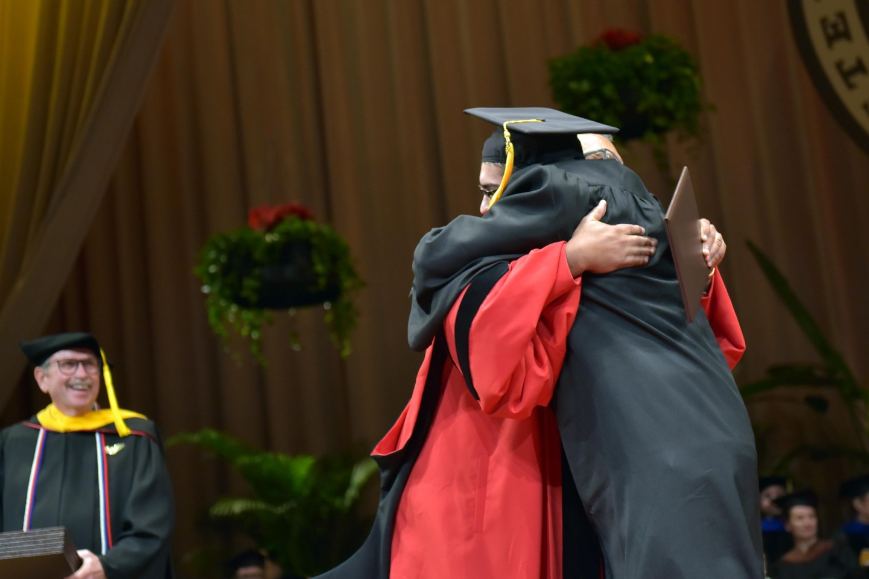 Dr. Edward Montgomery, WMU president, hugs a student at graduation.