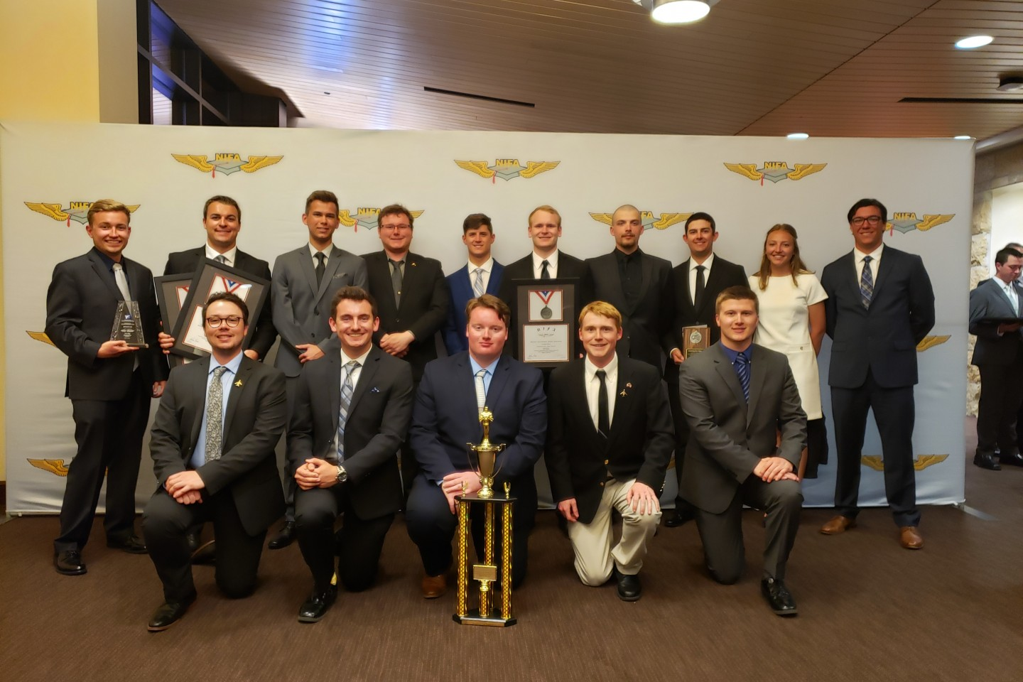 Photo of the 2019 Sky Bronco flight team posing with a trophy and various plaques.