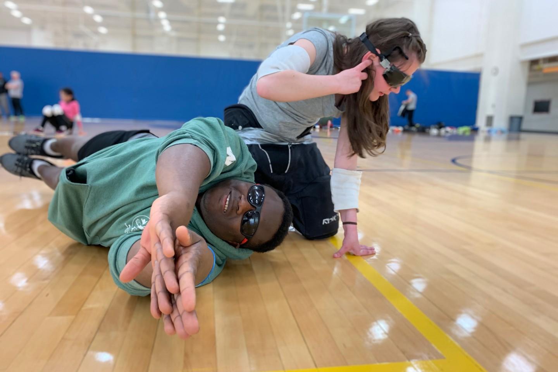 WMU student Osman Koroma teaches a girl how to play goalball.