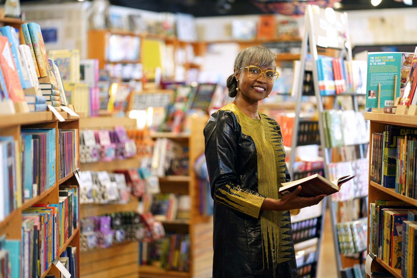 A woman stands in an aisle in a bookstore holding a book.