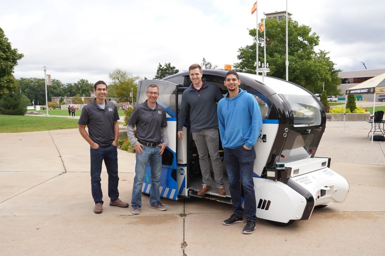 A research team stands next to an autonomous shuttle.