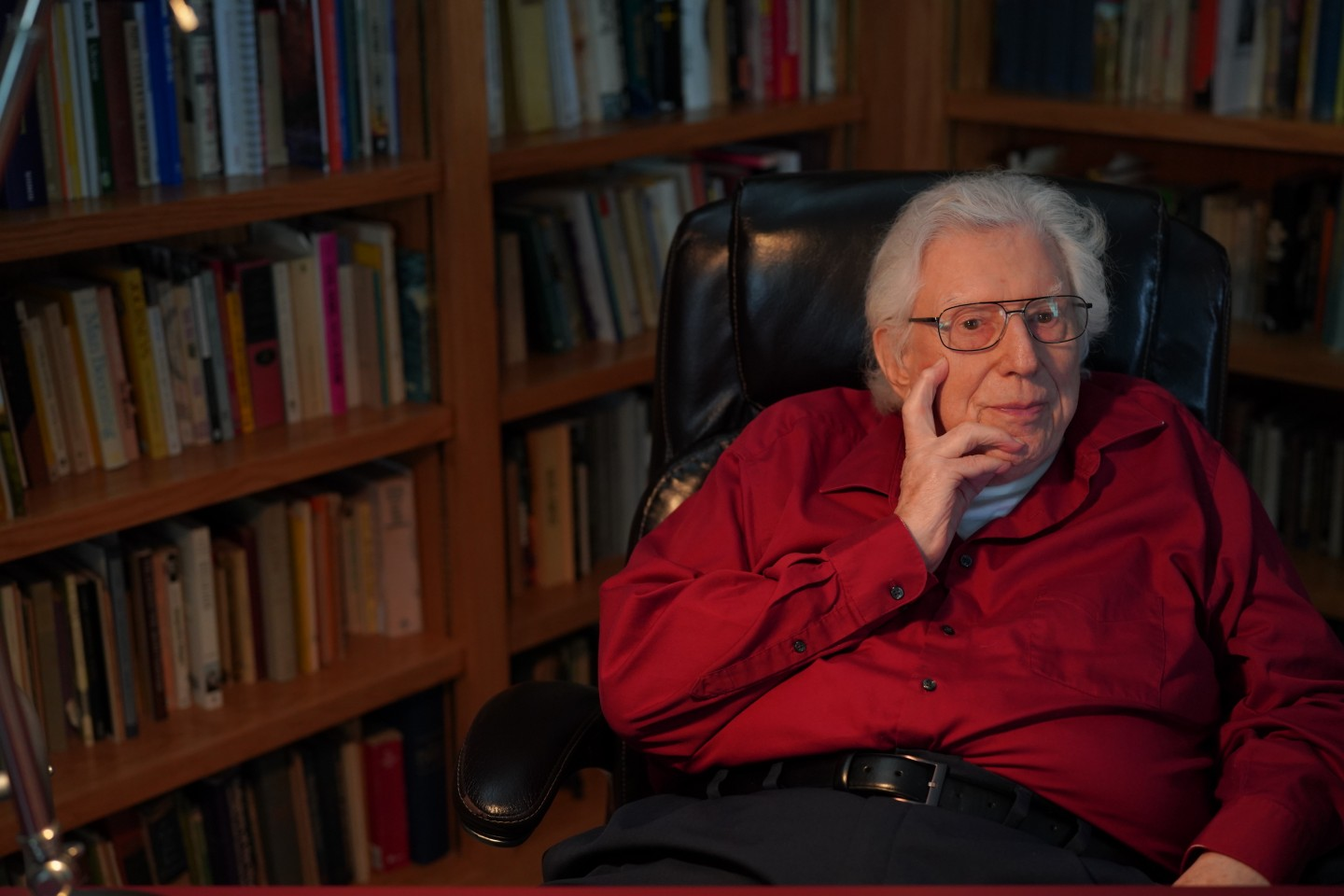Dr. Rudolf Siebert sits in his home office surrounded by book shelves.