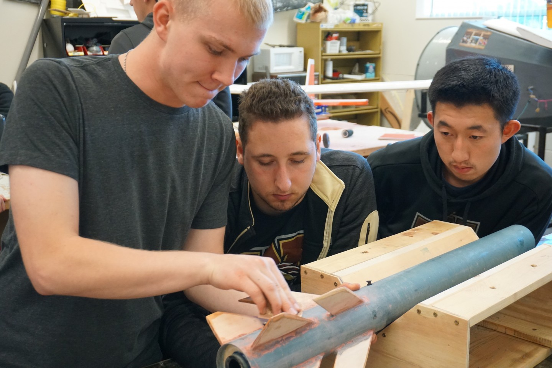Students sand a rocket.