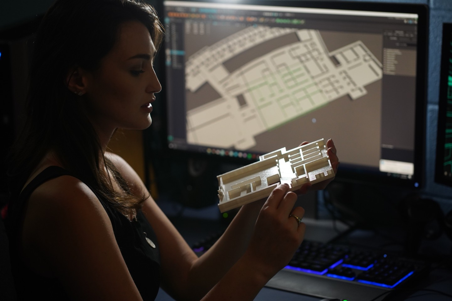 A student holds a 3D map prototype with a larger scale project on the computer screen in the background.