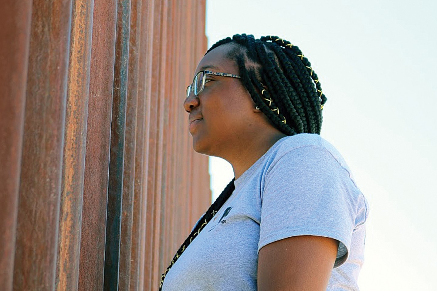 A student looks through the fence at the U.S.-Mexico border.