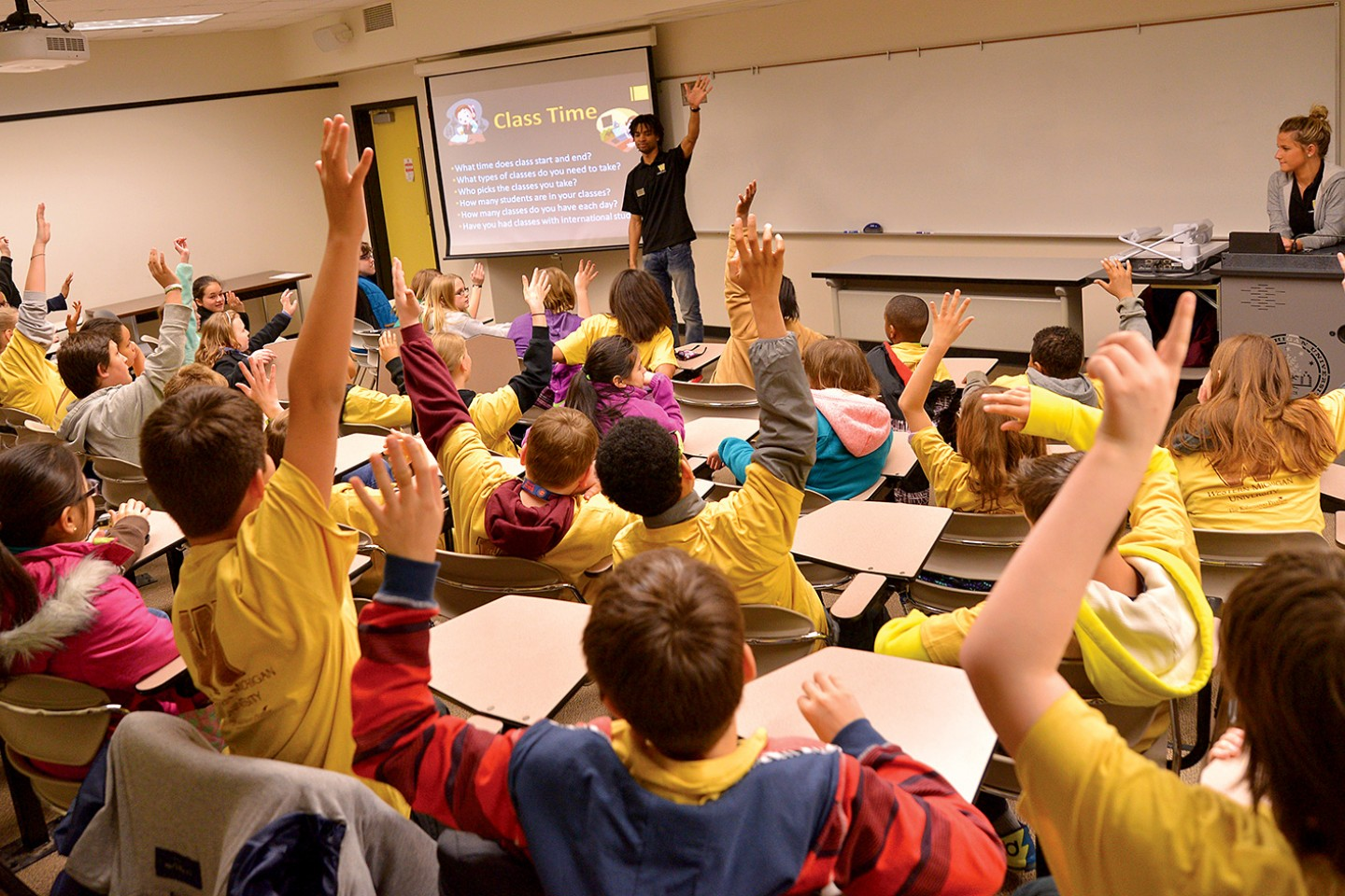 Photo of middle-school students sitting in a classroom and raising their hands.