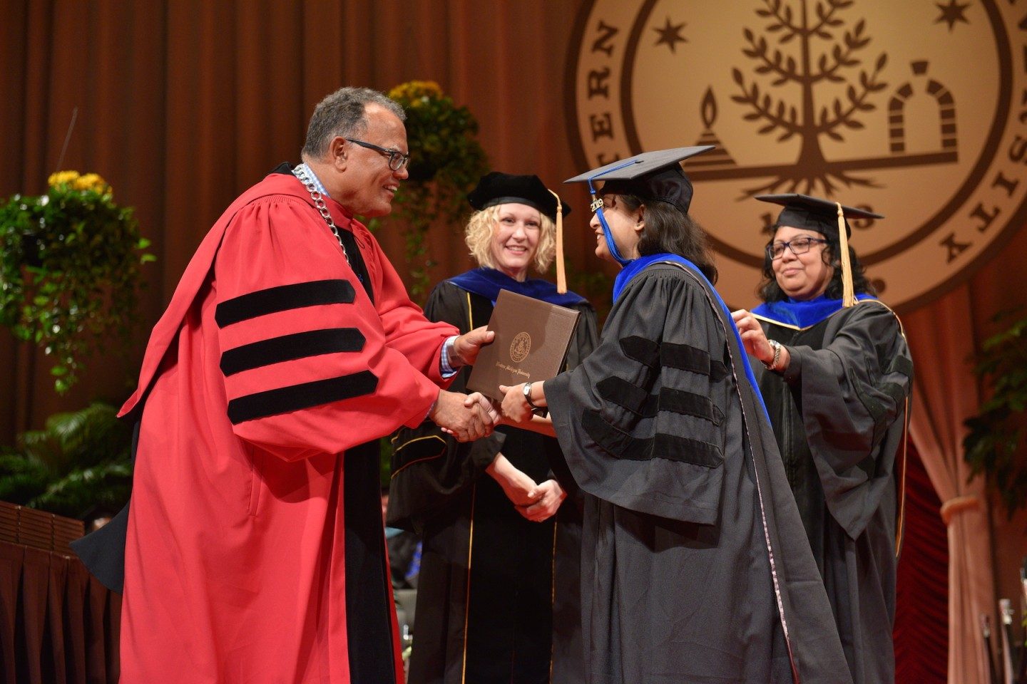 President Edward Montgomery shakes Dr. Dweepobotee Brahma's hand on the commencement stage.