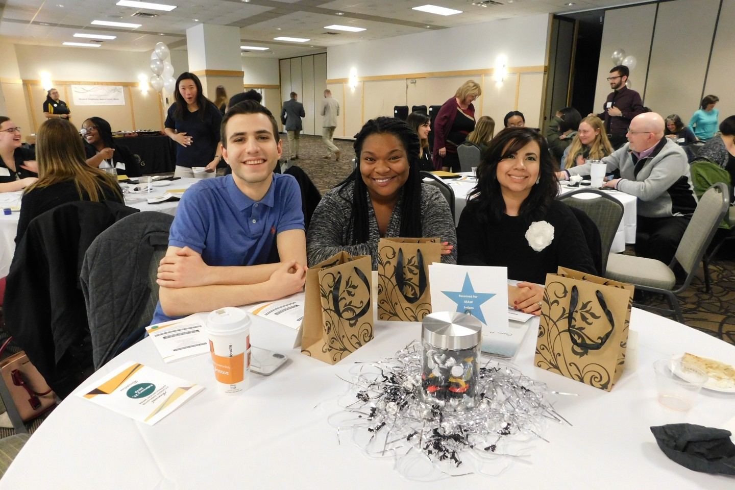 Photo of three people sitting at a table with decorations.
