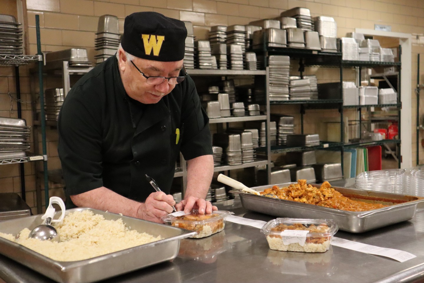 Rob Powers labels a meal that he packaged for the Invisible Need Project.