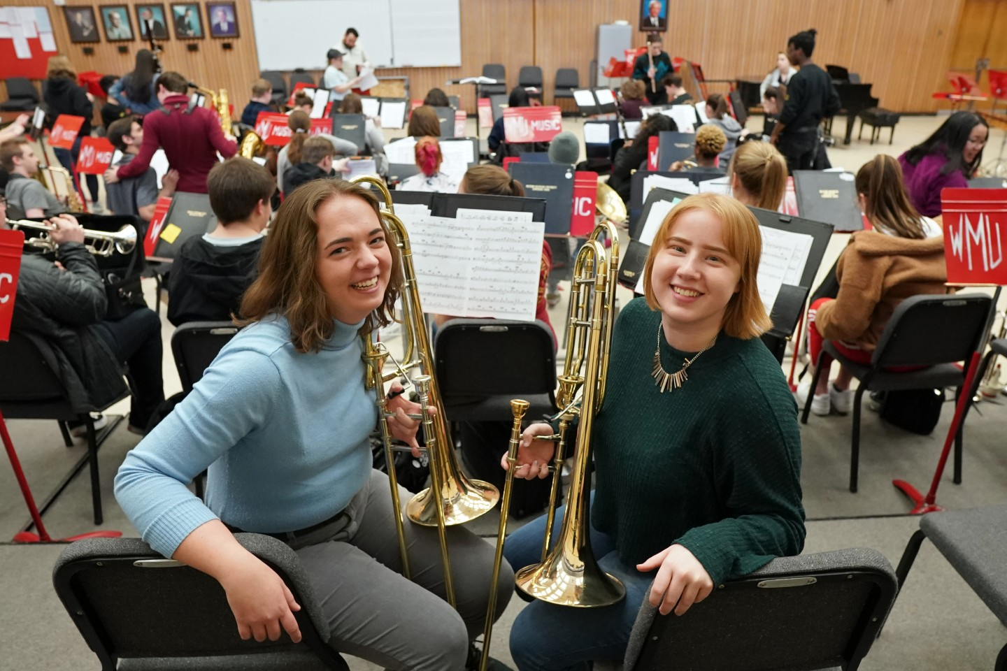 Alyson Johnson and Alayna O'Connell pose for a picture with their trombones.