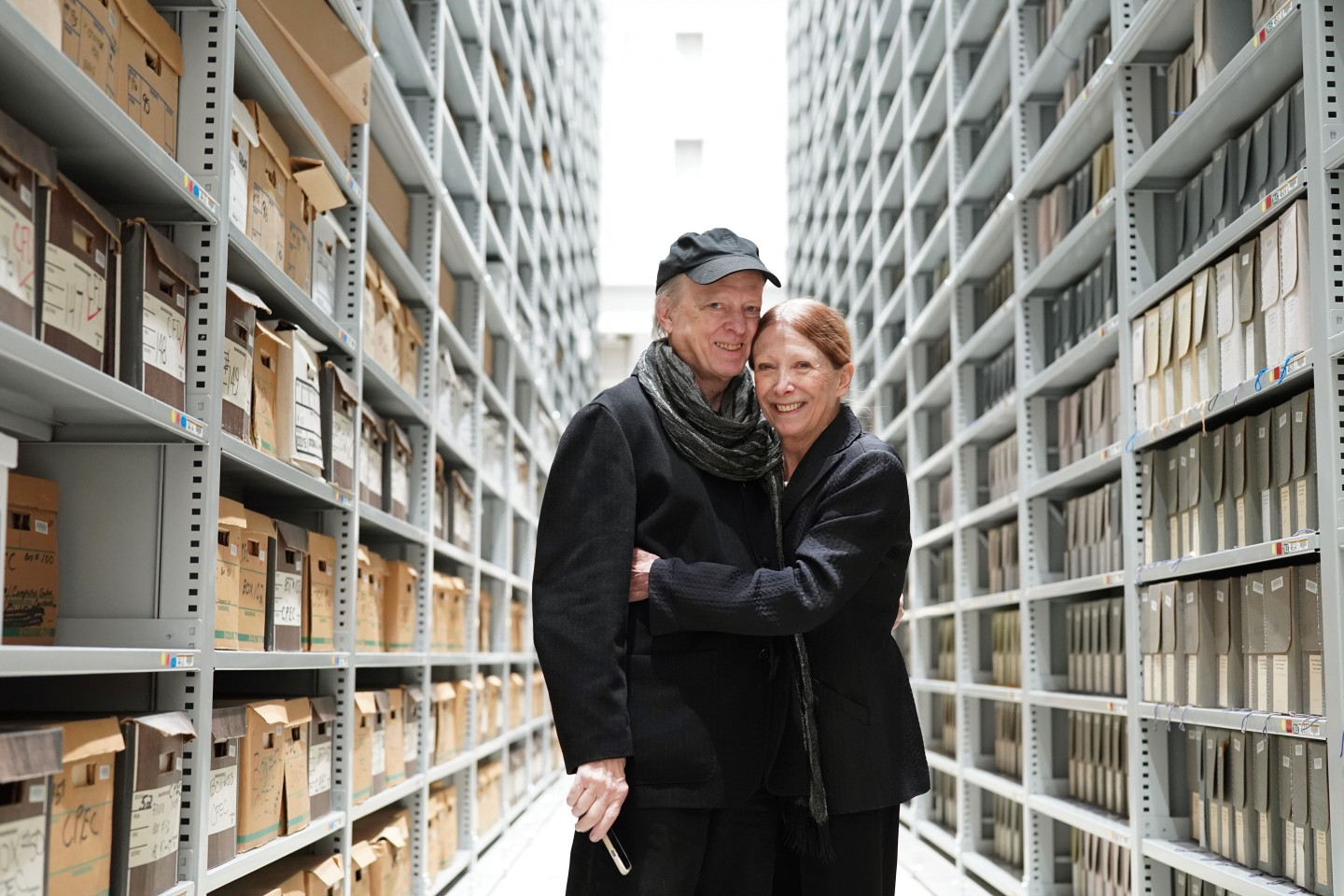 Photo of author and illustrator David Small and author Sarah Stewart standing between long sets of shevles.