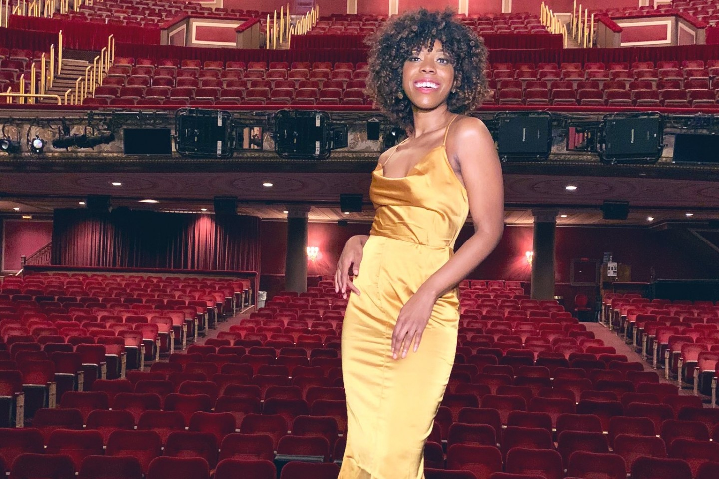 Tiffany Francés stands on stage at Broadway's Imperial Theatre.