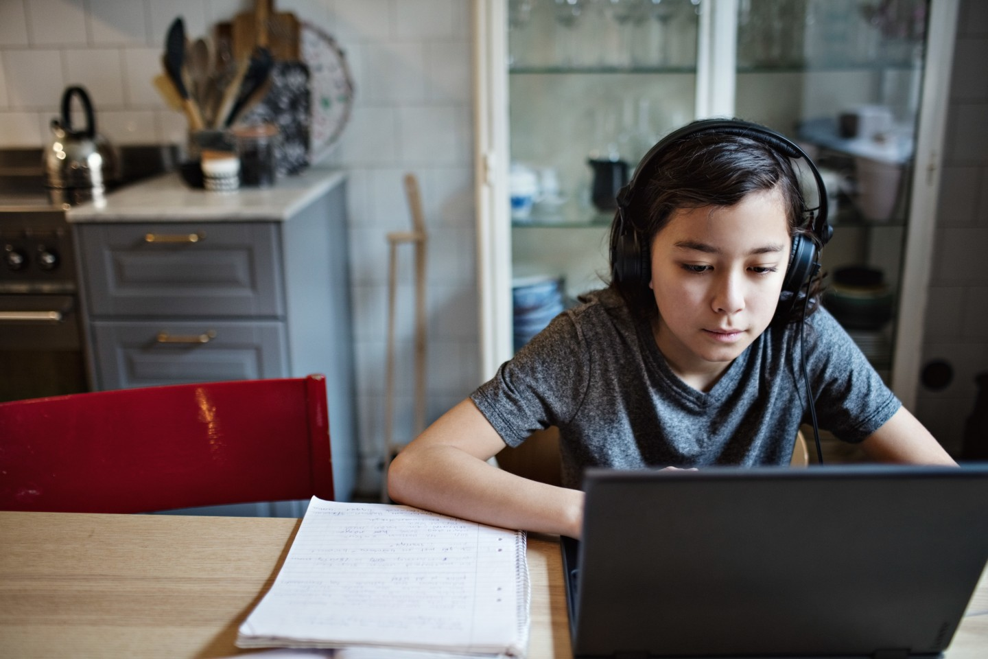 A child wears headphones as they sit at their laptop computer.