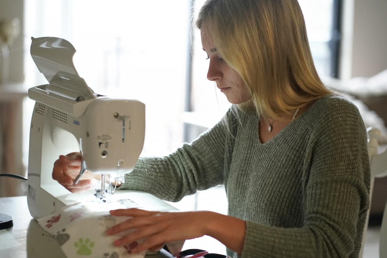 Al Mauriello sews a mask on her sewing machine.