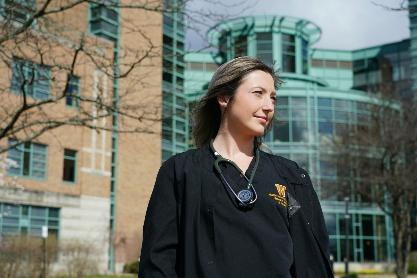 A nursing student stands outside with her stethoscope around her neck.
