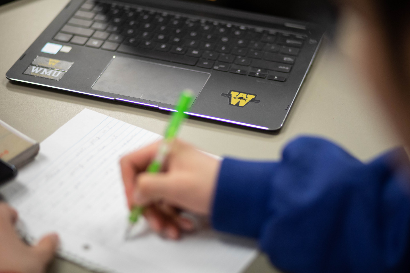 Photo of a laptop on a desk and a student's hand writing.