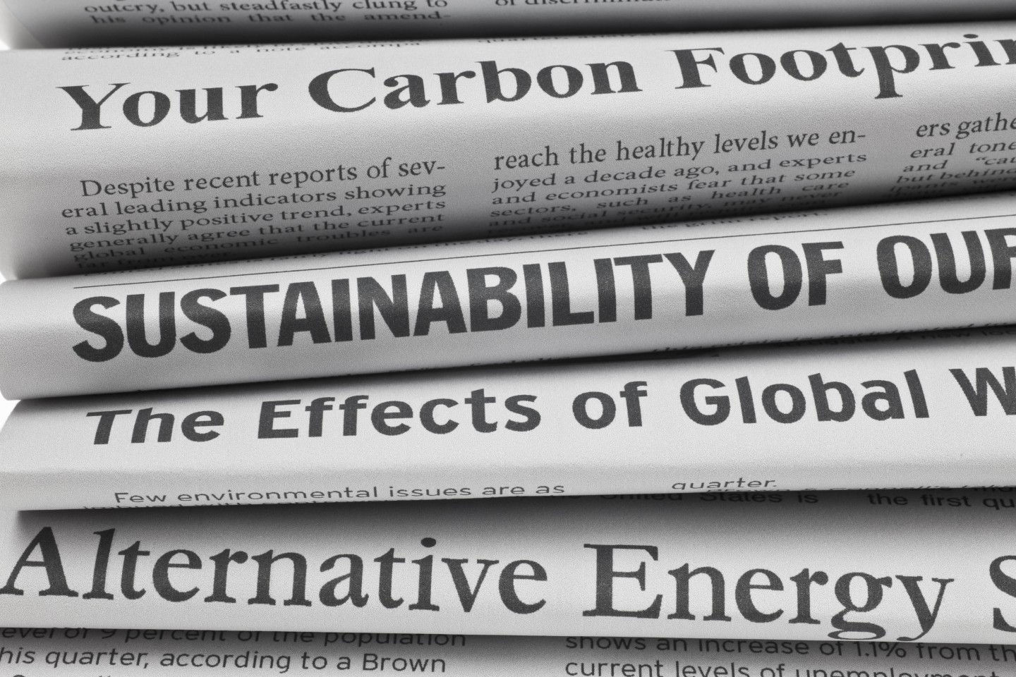 Image of a stcked pile of newspaers with headlines relating to climate change.